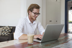 Young man sitting at home looking at his laptop Royalty Free Stock Images