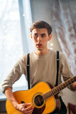 Young man sitting at home and playing guitar dramatic Royalty Free Stock Photos