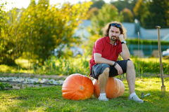 Young man sitting on huge pumpkins Royalty Free Stock Photos
