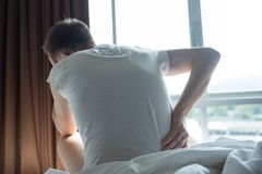 Young man sitting indoor on the bed feeling ache in his back. Young man wearing white t-shirt sitting indoor on the bed feeling sudden ache in his back stock photos