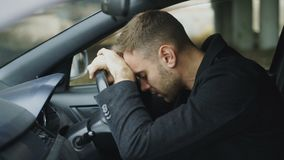 Young man sitting inside car is very upset and stressed. Young depresses man sitting inside car very upset and stressed after car accident outdoors stock footage