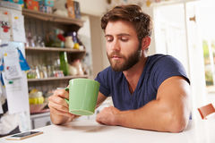 Young Man Sitting At Kitchen Table Drinking Coffee Stock Photo
