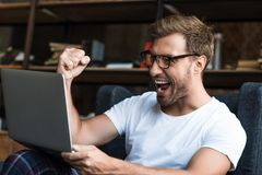 Young man sitting with laptop in armchair and cheering with his fist as he is looking royalty free stock images