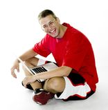 Young man sitting with laptop, laughing Royalty Free Stock Photography