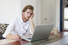 Young man sitting with laptop and looking sad Stock Images