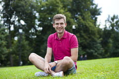 Young man sitting on the lawn in the summer park Stock Photography