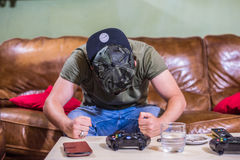 Angry gamer slamming his fists on the table. A young man sitting on a leather brown couch using a game controller. Playing video games at home. A sad and Stock Images