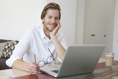 Young man sitting in living room with his laptop Stock Image