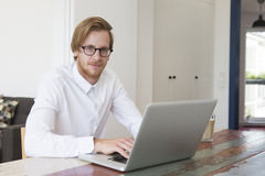 Young man sitting in living room with his laptop Royalty Free Stock Image