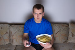 Young man sitting in living room and watching tv with chips Stock Photos