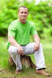 Young man sitting on a log Stock Images