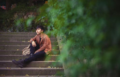 Young man sitting, loneliness, among the nature Royalty Free Stock Photography
