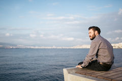 Young man sitting look at sea - Loneliness.  Royalty Free Stock Image