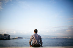 Young man sitting look at sea - Loneliness Stock Image