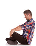 Young man sitting looking down. Side view of a casual cross legged young man looking down and holding his palms on his knees, on white Royalty Free Stock Image