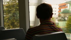 Young man sitting and looking at view through moving train window, commuting stock footage