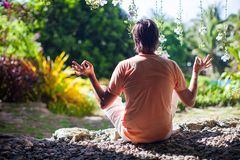 Young man sitting in the lotus position at Royalty Free Stock Images