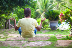 Young man sitting in the lotus position in the Stock Photography