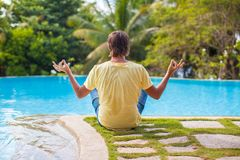 Young man sitting in lotus position near the pool Royalty Free Stock Photography