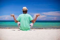 Young man sitting in lotus position on white sand Royalty Free Stock Photo