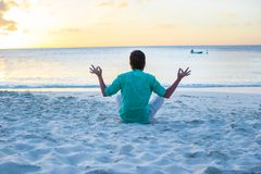 Young man sitting in lotus position on white sand Stock Photos