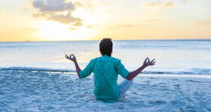 Young man sitting in lotus position on white sand Stock Photography