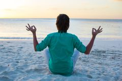 Young man sitting in lotus position on white sand Stock Image