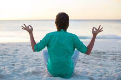 Young man sitting in lotus position on white sand Stock Images