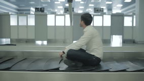 Young man sitting at the luggage conveyor stock video