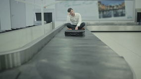 Young man sitting at the luggage conveyor and moving forward. The action takes place at the arriving hall of the airport at the baggage claim desk. Handsome stock footage