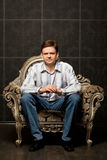 Young man sitting in magnificent ancient armchair Royalty Free Stock Images