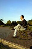 Young man sitting on the metal bench. Lonely young man sitting on the bench outdoors Royalty Free Stock Photography