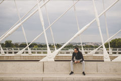 Young man sitting on the modern bridge in the city, using his smartphone.  Royalty Free Stock Image