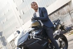 Young man sitting on motorcycle leaning on helmet looking aside serious stock image