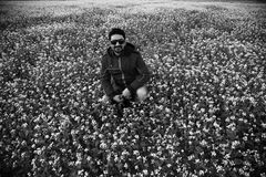 Young man sitting in a mustard crops field. A young man wearing sunglass sitting in a mustard crops field  unique black and white photo stock image
