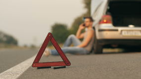Young man sitting near broken car with cell phone. Road trip car trouble. A young man with a silver car that broke down on the road stock footage