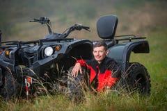 Young man sitting near four-wheeler ATV Royalty Free Stock Image