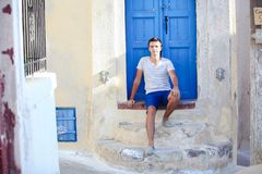 Young man sitting near old blue door of Emporio Royalty Free Stock Photography