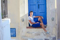 Young man sitting near old blue door of Emporio Stock Photography
