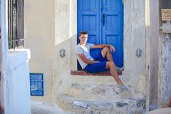 Young man sitting near old blue door of Emporio Stock Photos
