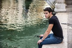 Young Man Sitting Next to Canal in Venice, Italy Stock Image