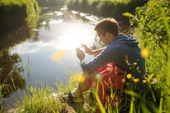 Young man sitting next to river with mobile phone and enjoying in summer Royalty Free Stock Image