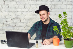 Young man sitting in office with a cup of coffee and vaping. Young man sitting in office with a cup of coffee, vaping and releases a cloud of vapor. Working at Stock Image