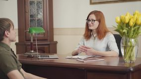 Young man sitting in the office of psychologist, back view. Attractive red-haired young female psychologist in glasses stock footage