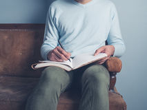 Young man sitting on old sofa writing. A young man is sitting on an old sofa and is writing in a notebook Royalty Free Stock Photos