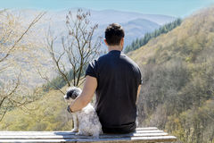 Young Man Sitting On A Bench With His Dog In The Mountain Stock Images