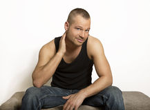 Young man sitting with one hand at his head. Looking at the camera, muscle shirt and jeans, well maintained and built, portrait Royalty Free Stock Photos