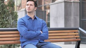 Young Man Sitting Outdoor on Bench. 4k high quality, 4k high quality stock video footage