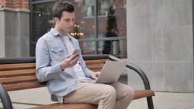 Young man sitting outdoor using smartphone and laptop stock footage