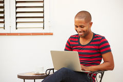 Young Man Sitting Outdoors With Laptop And Drinking Coffee Stock Images